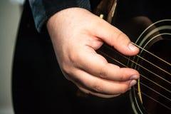 Dito del chitarrista che seleziona una chitarra immagine stock