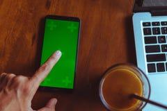 Dito del rubinetto dell'uomo sullo smartphone con lo schermo verde vicino Caffè, computer portatile sulla tavola Fotografia Stock