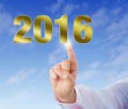 Dito indice che tocca un nuovo anno dorato 2016 Immagine Stock