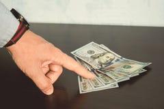 dito indice dell'uomo con la camicia blu che mostra o che indica i contanti dei soldi di valuta, Fotografia Stock