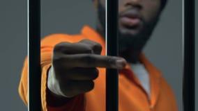 Dito medio di mostra criminale afroamericano arrabbiato attraverso la cella di prigione, conflitto video d archivio