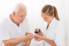 Dito paziente del ` s del dottore Using Glucometer On immagine stock libera da diritti