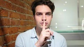 Dito sulle labbra, giovane che chiede il silenzio Fotografie Stock