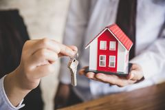 Ditt nya hus, tangent f?r fastighetsm?klareinnehavhus till hans klient, n?r underteckning av avtals?verenskommelse i regeringsst? royaltyfri fotografi