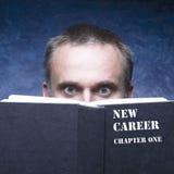 Ditt nya kapitel som är skriftligt på den svarta boken Mogen man bak boknolla royaltyfri bild