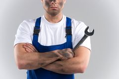 Dity young mechanic in blue overall on blue background. Stock Photography