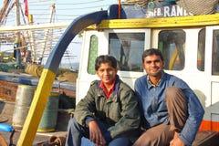 DIU,印度- 2014年1月8日:两位渔夫画象生和他们的渔船的儿子在Vanakbara捕鱼港口 免版税库存图片