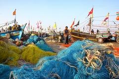 DIU, INDE - 9 JANVIER 2014 : Pêcheur travaillant à son filet au port de pêche de Vanakbara avec les filets de pêche colorés dans  Photos libres de droits