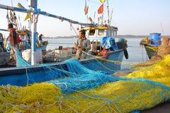 DIU, INDIA - JANUARI 9, 2014: Visser die aan zijn visnet bij de Vissershaven van Vanakbara in Diu-Eiland werken stock afbeeldingen