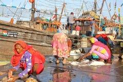 DIU, INDIA - JANUARI 8, 2014: Vrouwen die vissen voor verkoop voorbereiden bij de Vissershaven van Vanakbara in Diu-Eiland royalty-vrije stock foto