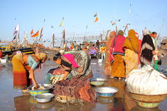 DIU, INDIA - JANUARY 8, 2014: Women preparing fish for sale at Vanakbara Fishing port in Diu Island Stock Photo