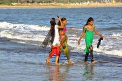DIU, LA INDIA - 6 DE ENERO DE 2014: Mujeres jovenes coloridas y hermosas que caminan en la costa en la isla de Diu Foto de archivo