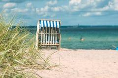 Diuna z niektóre tradycyjnymi drewnianymi plażowymi krzesłami na piaskowatej plaży i trawą Północny Niemcy na wybrzeżu Bałtycki, Obraz Stock