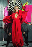 Diva in dress in wardrobe. One sexual attractive diva young woman in long red dress with deep low neck in jeans standing in wardrobe among many colorful bright Royalty Free Stock Photos