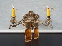 Diva, fragancia para las señoras, botella de perfume grande al lado de una botella de perfume comercial delante del candelabros c foto de archivo libre de regalías