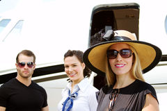 Diva lady with pilot and stewardess. By airplane Stock Photos