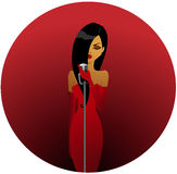 Diva in red. Beautiful brunette in elegant red dress holding a microphone Royalty Free Stock Photos