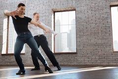 Divan charismatique de danse enseignant le tango vieillissant d'homme à la salle de bal Photographie stock
