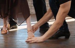Divan expérimenté de danse enseignant le tango vieillissant de couples dans la salle de bal Images stock