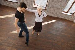 Divan flexible de danse aidant la femme âgée dans la salle de bal Photos stock