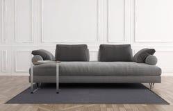 Divan gris dans une salle lambrissée par blanc Photos stock