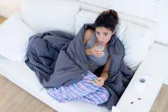 Divan menteur de malade de jeune femme hispanique attirante à la maison dans le froid et la grippe dans le symptôme de la maladie image libre de droits