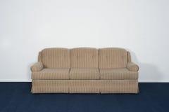 Divan ou Davenport, tapis bleu, mur blanc vide Images libres de droits