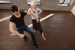 Divan sportif de danse enseignant le vieux retraité dans la salle de bal Photographie stock libre de droits