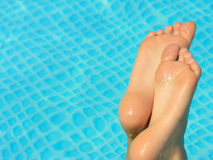 Dive in. Bare feet against a swimming  pool background Royalty Free Stock Image