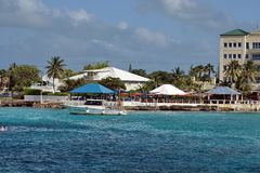 Dive boat in the harbor on Grand Cayman. Cayman Islands, with a waterfront bar in the background stock photography