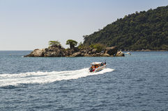 Dive boat heading to the island in a tropical sea Royalty Free Stock Photo