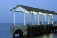 Dive boat jetty. Architectural details of concrete dive boat jetty on ocean illuminated at twilight stock photo