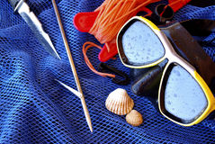 Dive Gear. Details of scuba-diving and spear-fishing gear over a blue fishing net bag Stock Image