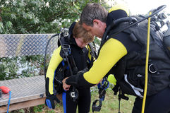 Dive instructor, the most beautiful job of the world. Scuba diving instructor checking the dive gear of a boy stock photo