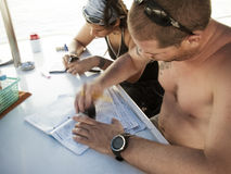 Dive instructor and student writing log books. KHAO LAK,, THAILAND - NOVEMBER 3: Dive instructor filling in log books after a dive on in Similan Islands on stock image