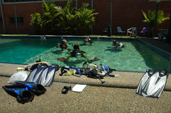 Dive learning. Four people practicing diving in small pool, diving equipment Stock Photos