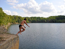 Dive. A man jumps from a ledge into the water Stock Photo