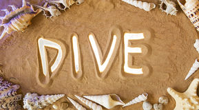 Dive symbol in the sand. Beach background. Top view. Dive in the Sand. Top view. Journey concept: Dive icon is Highlighted by Rays of Light. Beautiful Romantic royalty free stock photography