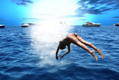 A dive towards the summer / Plunge. A dive towards the summer / A girl in costume plunges into the ocean Royalty Free Stock Photo