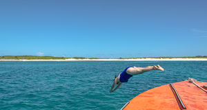 Dive In - Woman Dives Into Caribbean Sea. Tourist dives into clear blue ocean in sight of caye near the Caribbean island of Anguilla royalty free stock photography