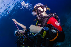 Diveguide with senior diver underwater Stock Photo