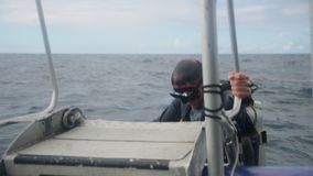 Diver boarding a boat from the sea. A shot of a diver rises from the sea. The diver is wearing a diving gear, complete with mask and oxygen tank. The diver stock footage