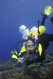 Diver with camera. In deep and bubbles stock photography