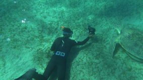 Diver with camera shooting sea turtle stock video footage