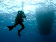 Diver Clearing Mask while Descending. Scuba Diver Clearing Mask while Descending under the Boat Stock Photo