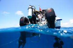 Diver climbing into a boat Stock Photos