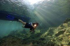 Diver, Diveboat & sunbeams. A female scuba diver with a torch in her hand is swimming below a diveboat. Rocky reef with diver in foreground, boat and sunbeams in royalty free stock photo
