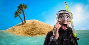 Diver in diving gear, desert island on background royalty free stock images