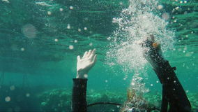 Diver emerges to the surface in the frame, hands are visible with a compensator button to control the ascent rate stock video footage