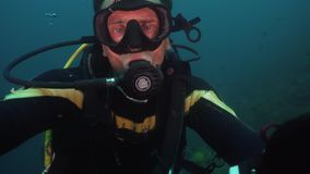 Diver under water. Diver in equipment with regulator in mouth under the water. Face diver in mask close-up stock video